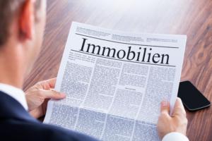Geschäftsmann liest Zeitung mit dem Titel Immobilien