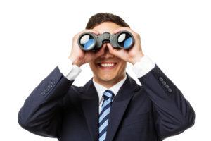 Geschäftsmann schaut durch Fernglas