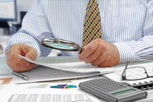 Männerhände mit Vergrößerungsglas – Datenanalyse bei Immobilienbewertung
